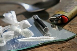 Narcotics on mirror with spoon and lighter in background
