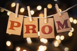 The word PROM printed on clothespin clipped cards in front of defocused glowing lights
