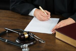 medical malpractice judge signing document near gavel stethoscope
