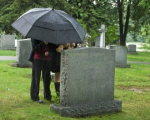 two people visiting a gravesite cemetery