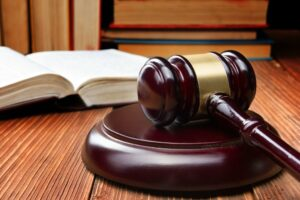 open-law-book-with-a-wooden-judges-gavel-on-table-in-a-courtroom-or-law-enforcement-office