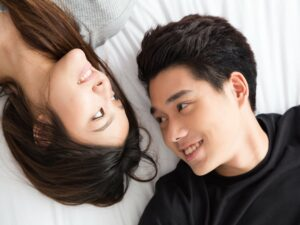 Young Asian Couple lying on the bed