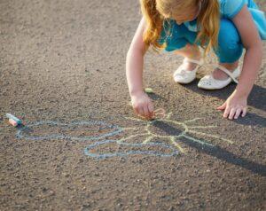 child drawing with chalk on asphalt